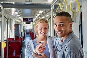 Junge Frau mit Handy in der Hand steht mit jungem Mann in der Bahn