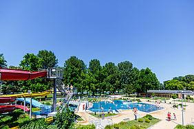 Das Rheinstrandbad in Rappenwört. Links im Bild ist eine rote Wasserrutsche zu sehen, rechts ein bleus Schweimmbcken und im Hintergrund ragen große Bäume in den wolkenlosen, blauen Himmel.