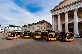 Fünf gelb-rote Busse stehen auf dem Marktplatz in Karlsruhe