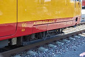 Gelb-roter Wagenkasten einer AVG-Stadtbahn und ein Schottergleis.