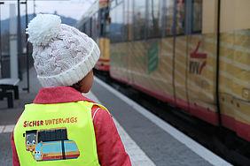 Kindergartenkind mit einer KVV-Warnwesteund weißer Mütze an einer Bahnhaltestelle