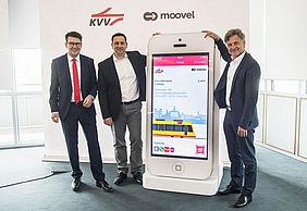Drei Männer stehen an einem riesigen Smartphone