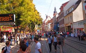 Die Pfinzalstraße in Durlach am verkaufsoffenen Sonntag: Menschen laufen an Verkaufsständen vorbei, rechts und links rahmen Häuser die Fußgängerzone ein.