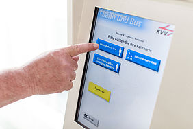 Ein ÖPNV-Kunde drückt mit seinem Zeigefinder auf das Display eines Fahrscheinautomaten.