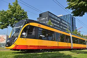 Eine Bahn (ET2010) steht vor einem Gebäude in Karlsruhe.