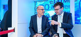Verkehrsminister Winfried Hermann und Herr Dr. Pischon unterhalten sich in einem autonom fahrenden Fahrzeug