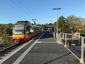 Der neue Bahnsteig am Schulzentrum Bretten und eine einfahrende Stadtbahn der AVG vor blauem Himmel