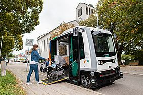 Eine Frau mit Kinderwagen steigt in das autonom fahrende EVA-Shuttle ein.