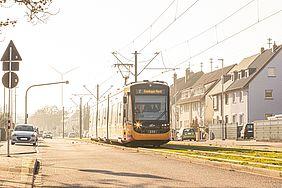 Eine Niederflurbahn der VBK fährt über das Rasengleis nach Knielingen Nord. Am Bildrand sind parkende Autos und Häuserfassaden zu sehen.