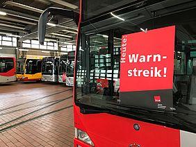 Busse in einer Wagenhalle. In der Frontschreibe eines Busses hängt ein rotes Plakat der Gewerkschaft ver.di.