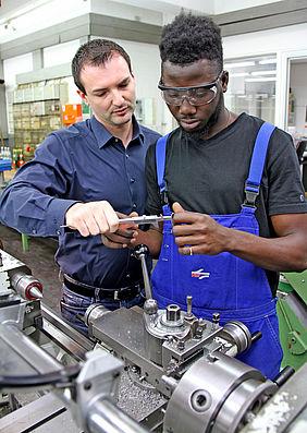 Zwei Männer stehen in der Werkstatt an einer Drehmaschine