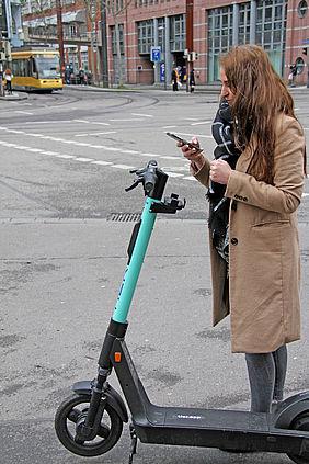 Frau steht mit einem E-Scooter auf der Straße und schaut auf ihr Handy